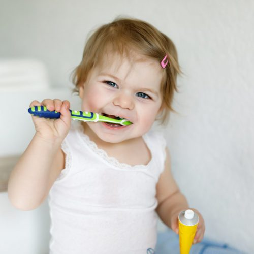Little baby girl holding toothbrush and brushing first teeth. Toddler learning to clean milk tooth. Prevention, hygiene and healthcare concept. Happy child in bathroom.