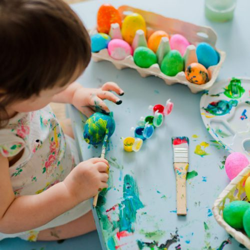 Child paints Easter eggs with a brush